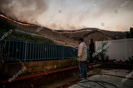 Noy (L) and his brother Mister P. (R) water the area outside their fence as the Blue Ridge Fire spreads in the hills near homes in Chino Hills, California, USA, 27 October 2020.
