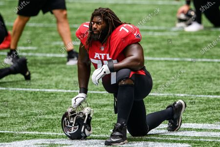 Atlanta Falcons offensive guard James Carpenter (77) stretches before an NFL football game against the Detroit Lions, in Atlanta. The Detroit Lions won 23-22