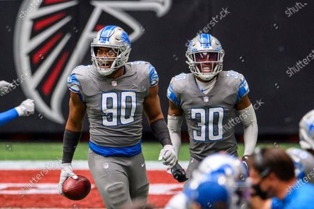 Detroit Lions defensive end Trey Flowers (90) and cornerback Jeff Okudah (30) celebrate during the second half of an NFL football game against the Atlanta Falcons, in Atlanta. The Detroit Lions won 23-22