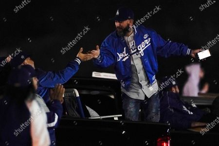 Baseball fans celebrate outside Dodger Stadium while watching the television broadcast of Game 6 of the World Series between the Los Angeles Dodgers and the Tampa Bay Rays, in Los Angeles
