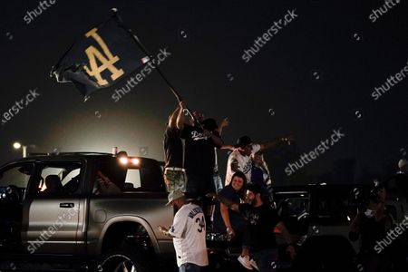 Fans celebrate outside Dodger Stadium while watching the television broadcast of Game 6 of the World Series between the Los Angeles Dodgers and the Tampa Bay Rays, in Los Angeles. The Dodgers won the series with a 3-1 victory Tuesday