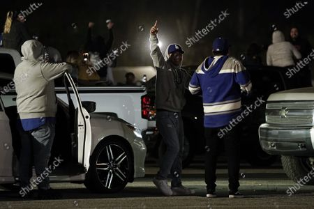 Fans celebrate outside Dodger Stadium while watching the television broadcast of Game 6 of the baseball World Series between the Los Angeles Dodgers and the Tampa Bay Rays, in Los Angeles. The Dodgers defeated the Rays 3-1, and won the series