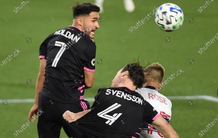 Seattle Sounders midfielder Cristian Roldan, left, heads the ball next to defender Gustav Svensson, center, and Vancouver Whitecaps midfielder Andy Rose during the second half of an MLS soccer match in Portland, Ore