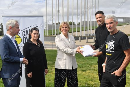 Stock Image of Former Australian soccer player Craig Foster (R) and National Rugby League (NRL) star Sonny Bill Williams (2-R) hand a petition to Independent Member for Warringah Zali Steggall during a media event outside Parliament House in Canberra, Australia, 28 October 2020. Craig Foster Sonny Bill Williams have jointly called on the Australian Government to accept New Zealand's offer to resettle refugees. The offer was made in 2013.