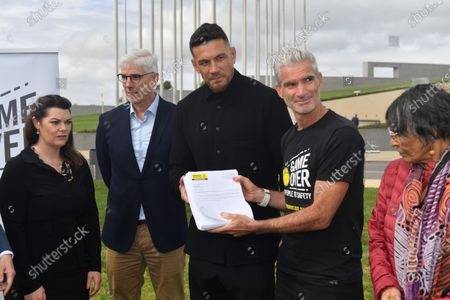 Former Australian soccer player Craig Foster (2-R) and National Rugby League (NRL) star Sonny Bill Williams (3-R) hold a petition during a media event outside Parliament House in Canberra, Australia, 28 October 2020. Craig Foster Sonny Bill Williams have jointly called on the Australian Government to accept New Zealand's offer to resettle refugees. The offer was made in 2013.