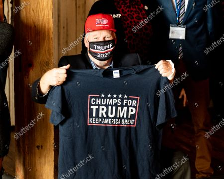 """A man with a """"Chumps for Trump"""" t-shirt attends a rally for Donald Trump for president at The Barn at Stoneybrooke."""