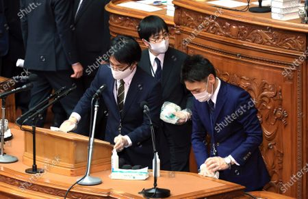Officers of Japan's Lower House disinfect microphones and a lectern after an opposition leader Yukio Edano of the Constitutional Democratic Party of Japan questioned to Prime Minister Yoshihide Suga at Lower House's plenary session at the National Diet in Tokyo on Wednesday, October 28, 2020. Suga delivered his first policy speech at the Diet on October 26.
