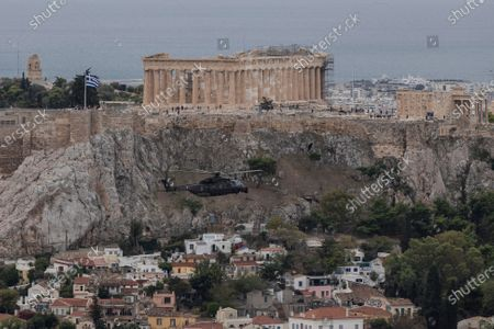 Military helicopter flies in front of the Parthenon temple on the ancient Acropolis hill in Athens, during a national holiday . The helicopters fly next to Acropolis hill to celebrate Greece's refusal to align itself with a belligerent fascist Italy in 1940 and instead fight a much stronger opponent, a decision which dragged it into World War II and eventually led to a brutal occupation by Nazi Germany