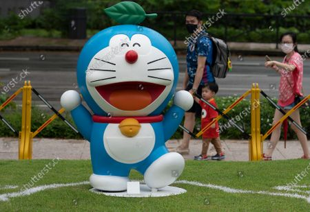 People walk past an exhibit from Doraemon's Time-Travelling Adventures exhibition at the National Museum of Singapore in Singapore, 28 October 2020. The year 2020 marks the 50th anniversary of the birth of the beloved Japanese manga character Doraemon from the popular animated series and comics of the same name. The exhibition featuring the robot cat cultural icon at the National Museum of Singapore will run until 27 December 2020.