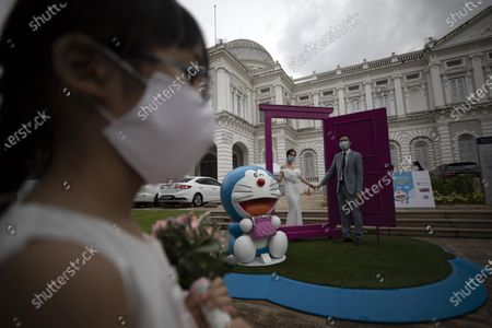 A flower girl looks on as a couple in their wedding dress pose for photos with an exhibit of Doraemon's Time-Travelling Adventures exhibition at the National Museum of Singapore in Singapore, 28 October 2020. The year 2020 marks the 50th anniversary of the birth of the beloved Japanese manga character Doraemon from the popular animated series and comics of the same name. The exhibition featuring the robot cat cultural icon at the National Museum of Singapore will run until 27 December 2020.