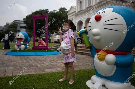 A girl pose for photos with exhibits from Doraemon's Time-Travelling Adventures exhibition at the National Museum of Singapore in Singapore, 28 October 2020. The year 2020 marks the 50th anniversary of the birth of the beloved Japanese manga character Doraemon from the popular animated series and comics of the same name. The exhibition featuring the robot cat cultural icon at the National Museum of Singapore will run until 27 December 2020.