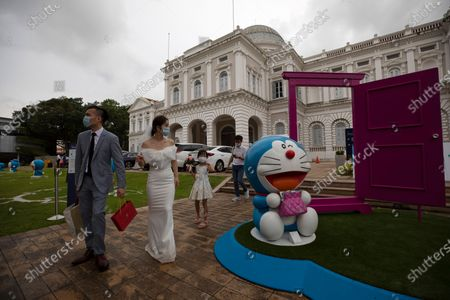 A couple in their wedding dress walk past an exhibit from Doraemon's Time-Travelling Adventures exhibition at the National Museum of Singapore in Singapore, 28 October 2020. The year 2020 marks the 50th anniversary of the birth of the beloved Japanese manga character Doraemon from the popular animated series and comics of the same name. The exhibition featuring the robot cat cultural icon at the National Museum of Singapore will run until 27 December 2020.