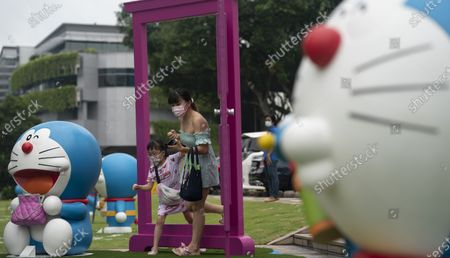 People pose for photos with exhibits from Doraemon's Time-Travelling Adventures exhibition at the National Museum of Singapore in Singapore, 28 October 2020. The year 2020 marks the 50th anniversary of the birth of the beloved Japanese manga character Doraemon from the popular animated series and comics of the same name. The exhibition featuring the robot cat cultural icon at the National Museum of Singapore will run until 27 December 2020.