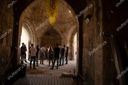 Group gathers under a work by American sculptor Dale Chihuly at the Tower of David Museum in the Old City of Jerusalem, . The ancient citadel is devoid of tourists due to the pandemic and undergoing a massive restoration and conservation project