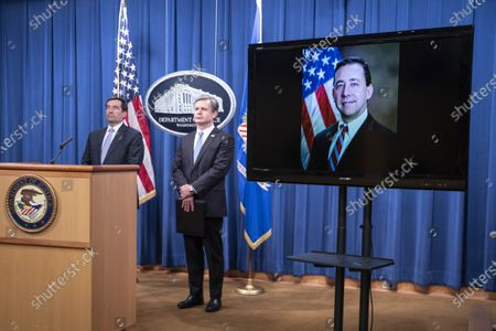 Assistant Attorney General for National Security John C. Demers, left, FBI Director Christopher Wray and Acting U.S. Attorney for the Eastern District of New York Seth DuCharme, pictured on screen as he attends virtually, participate in a news conference at the Department of Justice in Washington, DC, USA, 28 October 2020. Eight people have been arrested in connection to 'Operation Fox Hunt' an effort by China to threaten and coerce Chinese nationals viewed as threats to the regime to return to the country.