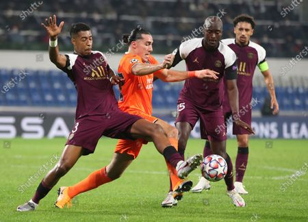PSG's Presnel Kimpembe, left, tries to block Basaksehir's Enzo Crivelli, center, during the Champions League group H soccer match between Basaksehir and Paris Saint Germain in Istanbul