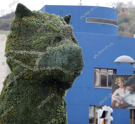 A large floral sculpture by US artist Jeff Koons of a puppy, known as 'Puppy,' that presides over the entrance of the Guggenheim Museum in Bilbao, Spain, 28 October 2020, wears the floral change that is usually made at fall, a flower mask as a gesture of empathy and encouragement to citizens to protect themselves during the Covid-19 coronavirus pandemic.