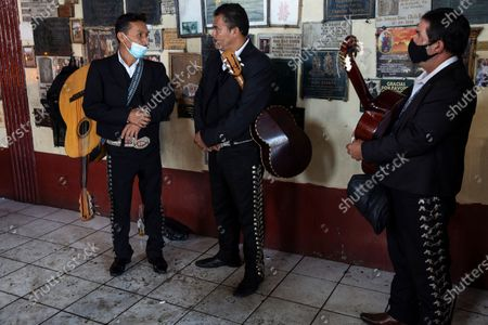Mariachi musicians wait for paying customers attending feast day celebrations for folk saint Maximon, an Indigenous character worshipped mainly by Indigenous people, inside the temple known as Maximon church in San Andres Itzapa, Guatemala, . To help curb the spread of the new coronavirus, the festival was limited to local residents who waited in line to enter little by little, and it was closed to pilgrims who travel here from across the country
