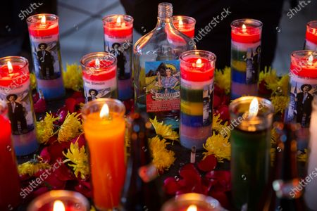 Bottle of liquor is surrounded by burning candles with images of folk saint Maximon, an Indigenous character worshipped mainly by Indigenous people, inside a temple known as Maximon church on his feast day in San Andres Itzapa, Guatemala, . To help curb the spread of the new coronavirus, the festival was limited to local residents who waited in line to enter little by little, and it was closed to pilgrims who travel here from across the country