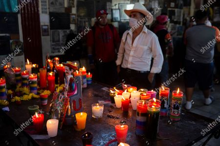 Man prays before a statue of folk saint Maximon, an Indigenous character worshipped mainly by Indigenous people, on his feast day inside a temple known as Maximon church in San Andres Itzapa, Guatemala, . To help curb the spread of the new coronavirus, the festival was limited to local residents who waited in line to enter little by little, and it was closed to pilgrims who travel here from across the country