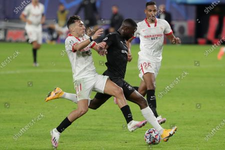 Rennes' James Lea Siliki, center, duels for the ball with Sevilla's Munir El Haddadi, left, during the Champions League group E soccer match between Sevilla and Rennes at the Ramon Sanchez Pijuan stadium in Seville, Spain