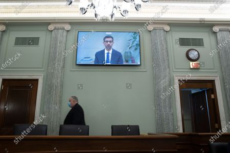 Senate staffers walk by as CEO of Alphabet Inc. and its subsidiary Google LLC, Sundar Pichai, appears on a monitor as he testifies remotely during the Senate Commerce, Science, and Transportation Committee hearing 'Does Section 230's Sweeping Immunity Enable Big Tech Bad Behavior?', on Capitol Hill in Washington, DC, USA, 28. CEO of Twitter Jack Dorsey; CEO of Alphabet Inc. and its subsidiary Google LLC, Sundar Pichai; and CEO of Facebook Mark Zuckerberg all testified virtually at the hearing. Section 230 of the Communications Decency Act guarantees that tech companies can not be sued for content on their platforms, but the Justice Department has suggested limiting this legislation.