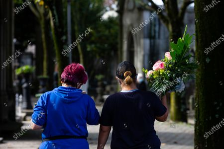 Women are seen carrying flowers at Agramonte cemetery before the All Saints'Day national holiday. People all over Portugal are allowed to visit the cemetery before All Saints'Day national holiday to pay tribute to their deceased relatives due to the covid 19 restrictions of traveling outside their living area in Porto, Portugal.
