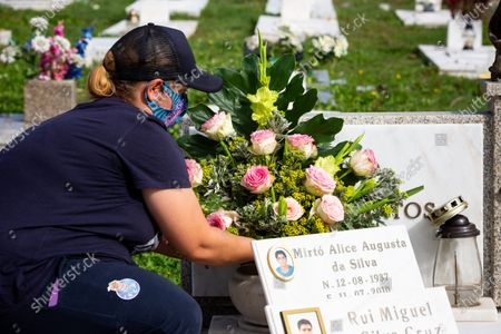 A woman wearing a face mask is seen putting flowers at a grave at Agramonte cemetery before All Saints'Day national holiday. People all over Portugal are allowed to visit the cemetery before All Saints'Day national holiday to pay tribute to their deceased relatives due to the covid 19 restrictions of traveling outside their living area in Porto, Portugal.