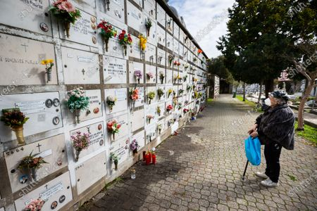 An elderly woman wearing a face mask pays tribute to her deceased relative at Agramonte cemetery before the All Saints'Day national holiday. People all over Portugal are allowed to visit the cemetery before All Saints'Day national holiday to pay tribute to their deceased relatives due to the covid 19 restrictions of traveling outside their living area in Porto, Portugal.