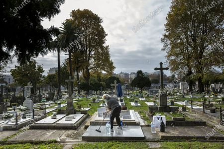 A woman wearing a face mask is seen cleaning the grave at Agramonte cemetery before All Saints' Day national holiday. People all over Portugal are allowed to visit the cemetery before All Saints'Day national holiday to pay tribute to their deceased relatives due to the covid 19 restrictions of traveling outside their living area in Porto, Portugal.