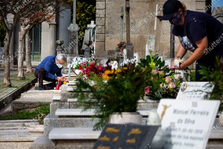 People wearing face masks are seen cleaning the graves at Agramonte cemetery before All Saints' Day national holiday. People all over Portugal are allowed to visit the cemetery before All Saints'Day national holiday to pay tribute to their deceased relatives due to the covid 19 restrictions of traveling outside their living area in Porto, Portugal.