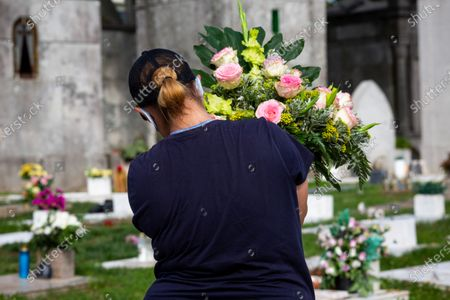 A woman is seen carrying flowers at Agramonte cemetery before the All Saints' Day national holiday. People all over Portugal are allowed to visit the cemetery before All Saints'Day national holiday to pay tribute to their deceased relatives due to the covid 19 restrictions of traveling outside their living area in Porto, Portugal.