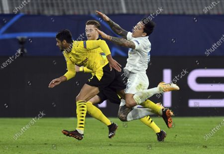 Dortmund's Mahmoud Dahoud, left, and Marco Reus, center, fight for the ball with Zenit's Sebastian Driussi, right, during the Champions League group F soccer match between Borussia Dortmund and Zenit Saint Petersburg in Dortmund, Germany