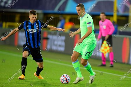 Lazio's Adam Marusic, right, vies for the ball with Brugge's Eduard Sobol during the Champions League Group F soccer match between Brugge and Lazio at the Jan Breydel stadium in Bruges, Belgium