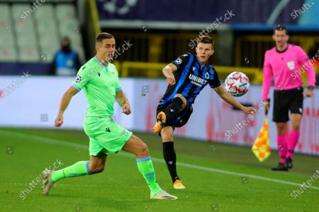 Brugge's Eduard Sobol, right, shoots the ball next to Lazio's Adam Marusic during the Champions League Group F soccer match between Brugge and Lazio at the Jan Breydel stadium in Bruges, Belgium