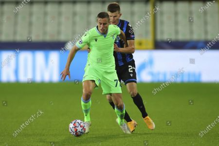 Lazio's Adam Marusic, left, vies for the ball with Brugge's Eduard Sobol during the Champions League Group F soccer match between Brugge and Lazio at the Jan Breydel stadium in Bruges, Belgium