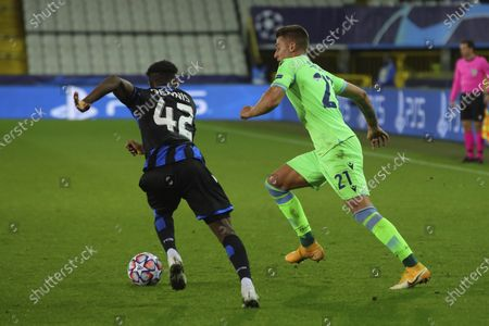 Lazio's Sergej Milinkovic-Savic, right, vies for the ball with Brugge's Emmanuel Dennis during the Champions League Group F soccer match between Brugge and Lazio at the Jan Breydel stadium in Bruges, Belgium