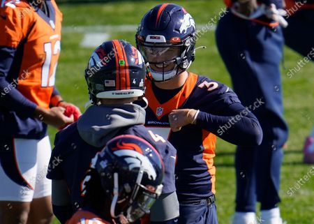 Denver Broncos starting quarterbck Drew Lock, back, chats with backup quarterback Brett Rypien as they take part in drills during an NFL football practice, at the team's headquarters in Englewood, Colo
