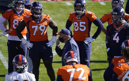 Denver Broncos head coach Viuc Fangio, center, talks with players before they take part in drills during an NFL football practice, at the team's headquarters in Englewood, Colo