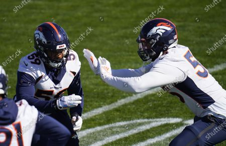 Denver Broncos outside linebackers Malik Reed, left, and Bradley Chubb take part in drills during an NFL football practice, at the team's headquarters in Englewood, Colo