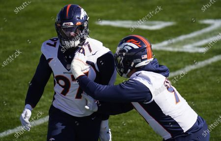 Denver Broncos outside linebackers Jeremiah Attaochu, left, and Anthony Chickillo take part in drills during an NFL football practice, at the team's headquarters in Englewood, Colo