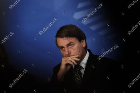 Brazil's President Jair Bolsonaro rubs his mouth during a ceremony to commemorate Public Servant Day, at the Planalto Presidential Palace in Brasilia, Brazil