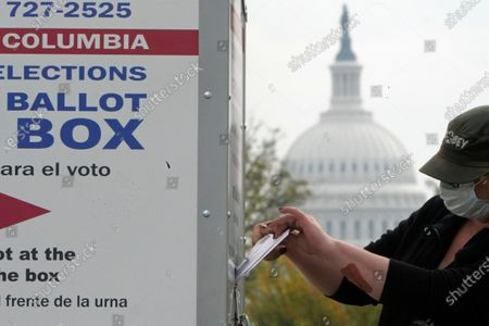 With the U.S. Capitol dome visible, a voter drops a ballot into an early voting drop box, at Union Market in Washington