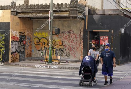 Pedestrians walk past graffiti sprayed during last night's fan celebrations after the Los Angeles Dodgers won the World Series, in downtown Los Angeles