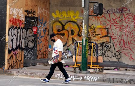 Los Angeles Dodgers fan walks past graffiti sprayed during last night's fan celebrations after the Los Angeles Dodgers won the World Series, in downtown Los Angeles