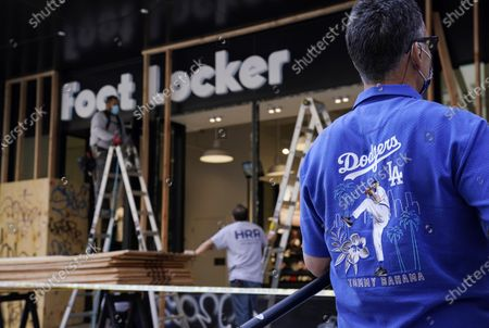 Reporter wears a Los Angeles Dodgers shirt outside a Foot Locker store that was looted and vandalized during fan celebrations following the Dodgers' World Series win, in Los Angeles