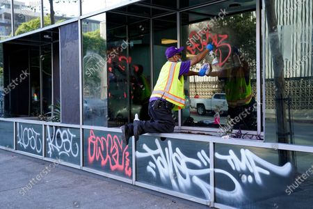 Manny Ramos cleans graffiti from an office building that was vandalized during fan celebrations following the Los Angeles Dodgers' World Series win, in Los Angeles
