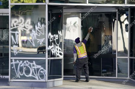 Worker cleans off graffiti sprayed onto an office building during last night's fan celebrations following the Los Angeles Dodgers' World Series win, in Los Angeles