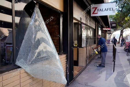 Smashed window stands near Z Falafel restaurant employee Sergio Duarte as he repairs a security gate that was damaged during last night's fan celebrations following the Los Angeles Dodgers' World Series win, in Los Angeles