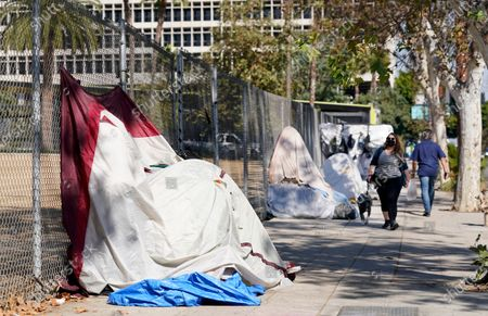 Pedestrians walk past a homeless encampment just outside Grand Park, in Los Angeles. Los Angeles is again considering a proposal to greatly restrict where homeless people may camp in public places around Los Angeles - rules that opponents say would criminalize homelessnessstockfotója